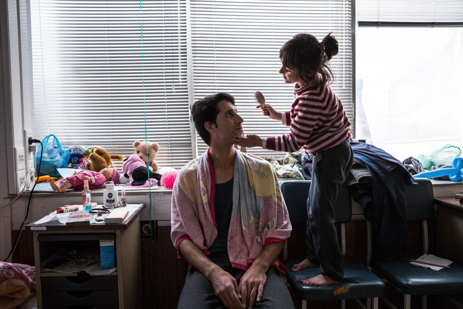 Hadis (6) menyisiri rambut ayahnya. Orang tua tunggal ini, Iman (31), lari dari Iran karena dia dan anaknya beragama Kristen. Saat batas-batas negara ditutup, dia mencari pengungsian di Yunani namun mungkin dalam beberapa tahun dia akan pindah ke Findlandia, tempat saudara perempuannya tinggal.